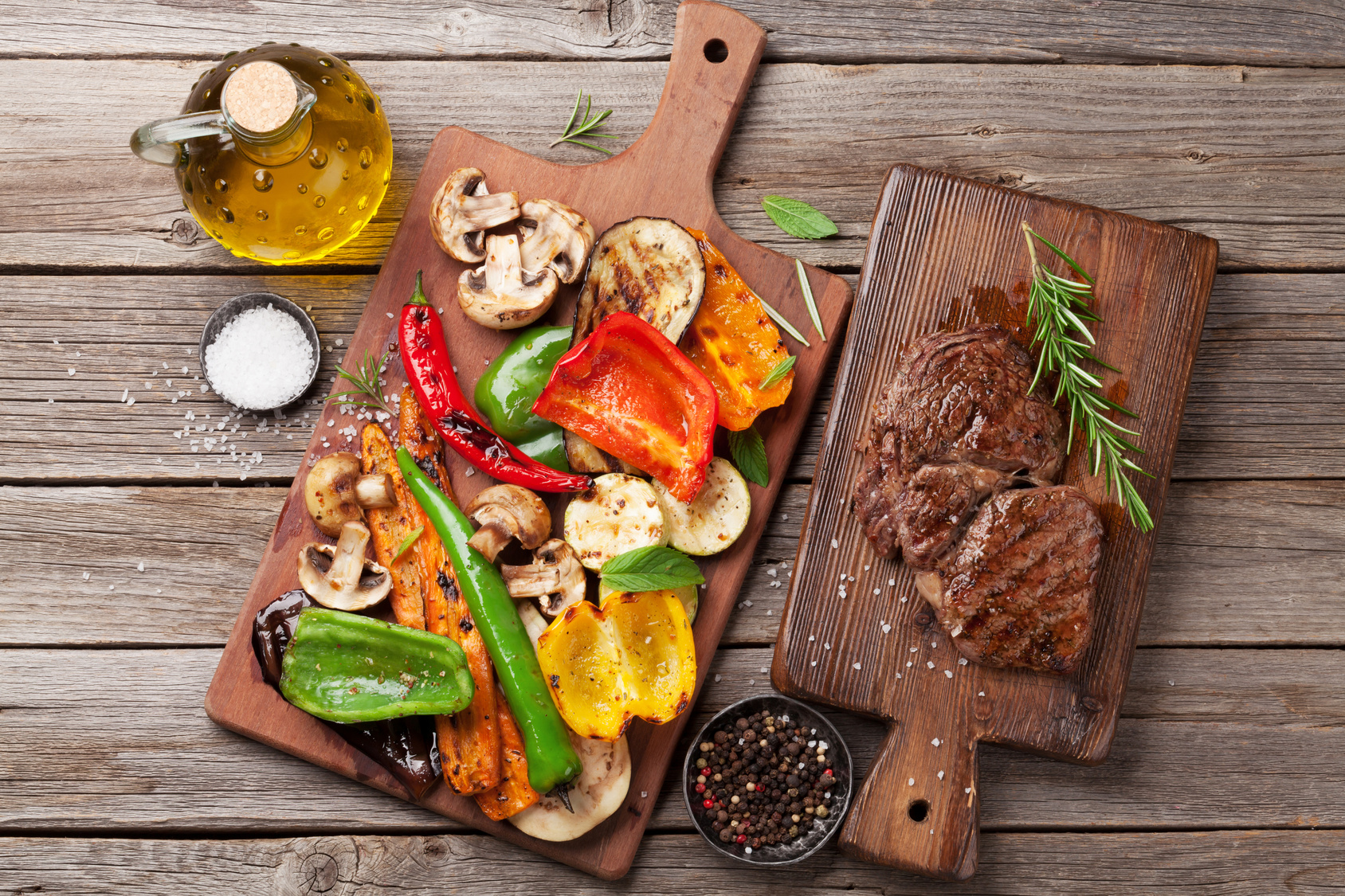 Grilled vegetables and beef steak on cutting board on wooden table. Top view